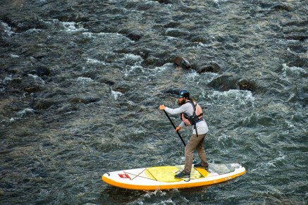 Kim Chatfield stand up paddle boards on the Rio Grande Gorge near Pilar