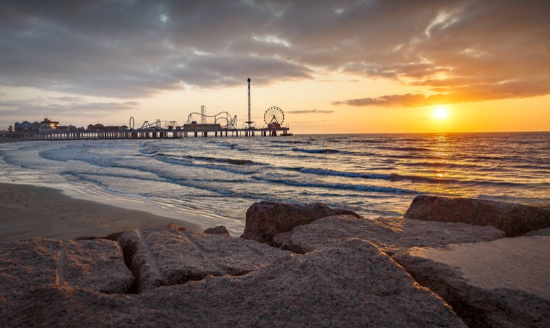 A Pleasure Pier sunrise in Galveston, Texas. Photo by Tim Stanley Photography.