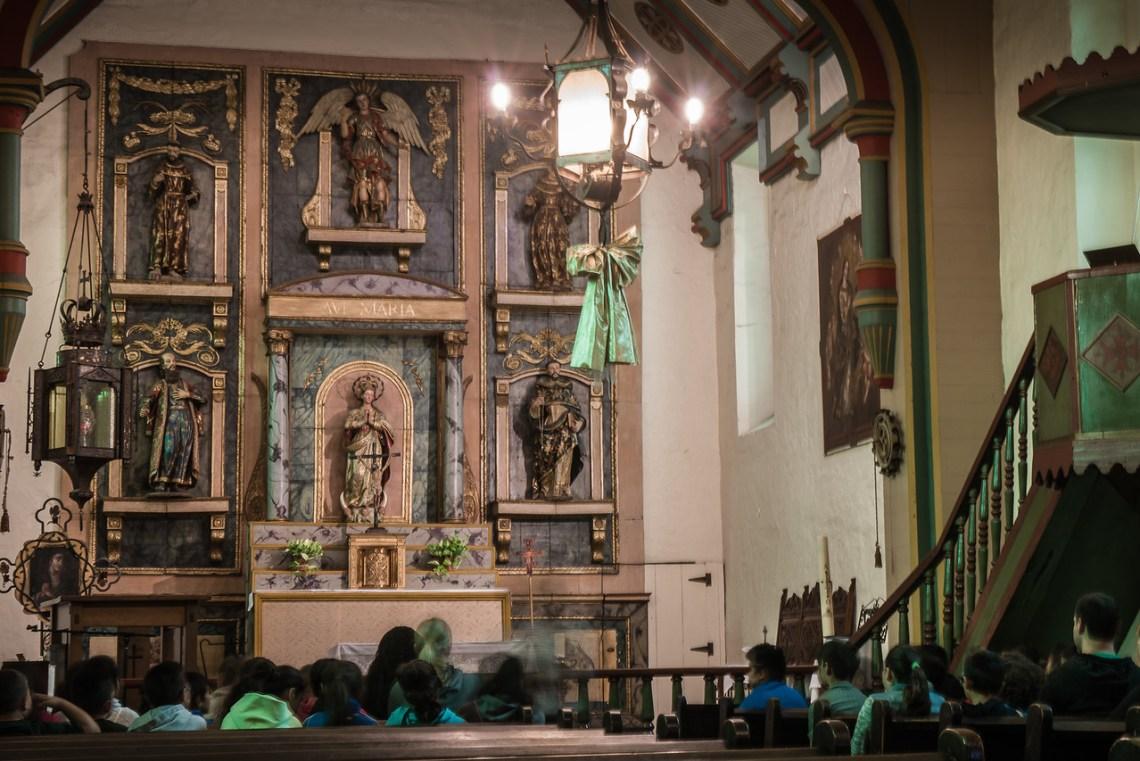 Docent speaking inside San Gabriel Arcangel