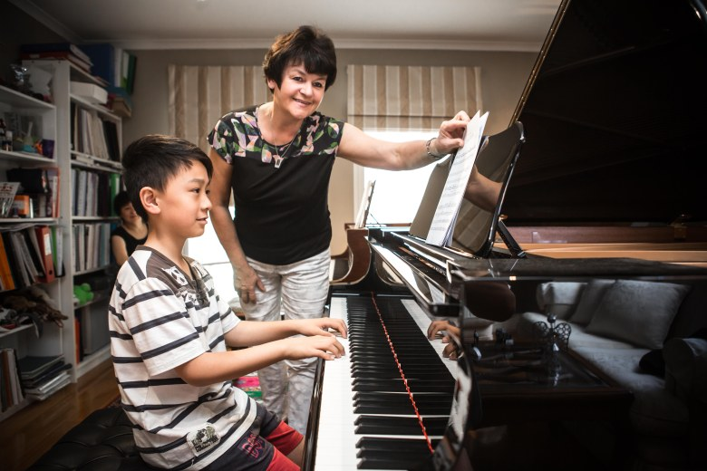 studio gallery teacher and student playing the piano