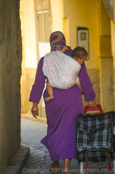 Moroccan woman carrying baby in the medina at Fez, Morocco