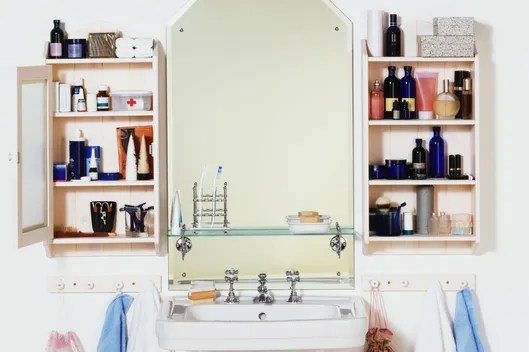 Bathroom sink, cupboards containing cosmetics and toiletries either side of mirror, towels hanging from wooden pegs.