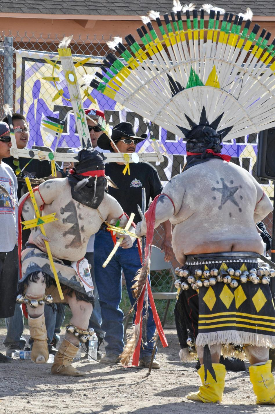 The San Carlos Apache Crown Dancers paint during the daylight and