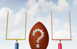 Winning strategy choice as two american football goal posts and a ball with a question mark made from stitching as a business goal symbol of uncertainty.