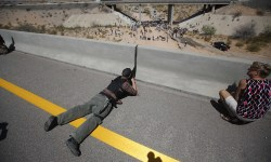 Parker from central Idaho aims his weapon from a bridge as protesters gather by the Bureau of Land Management&#