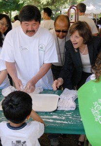 Glenn Kobata (left), an environmental scientist with CDFA's Feed Laboratory does a bit of simple chemistry for the kids along with CDFA Branch Chief Nirmal Saini (center) and CDFA Secretary Karen Ross.