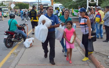 Venezuelans carry bags of toilet paper home on Saturday, Aug. 13, 2016, after Colombia and Venezuela agreed to formally reopen their borders for the first time in almost a year. (Jim Wyss/Miami Herald/TNS)