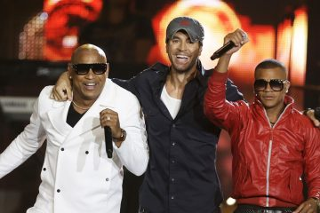 """FILE - In this April 24, 2014 file photo, Alexander Delgado, left, and Randy Malcom, right, of Cuban reggaton duo Gente de Zona, perform with singer Enrique Iglesias, during the Latin Billboard Awards, in Coral Gables, Fla. A collaboration between Iglesias and Descemer Bueno was recognized with five Latin Grammy nominations on Wednesday, Sept. 24, 2014, four of them for the megahit """"Bailando,"""" also featuring Gente de Zona, and one for the song """"Loco."""" (AP Photo/Lynne Sladky, File)"""