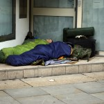 © AshleyNomad | Dreamstime.com - Homeless People Sleeping In A Doorway Photo