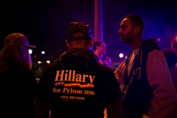 """Right across from the entrance of Washington University, Trump supporters have set up a display titled """"Hillary's House of Horrors"""". Two police vehicles are parked right next to it, with the officers out of the vehicles. An African American couple talks to two supporters about their political leanings."""