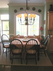 Square kitchen table is framed by and arched window