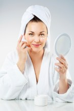 Woman putting on skin products with mirror