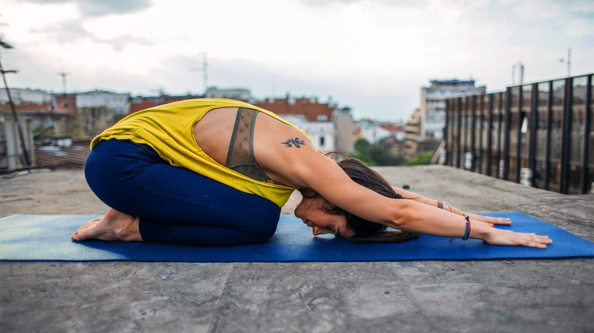woman with a new tattoo doing yoga