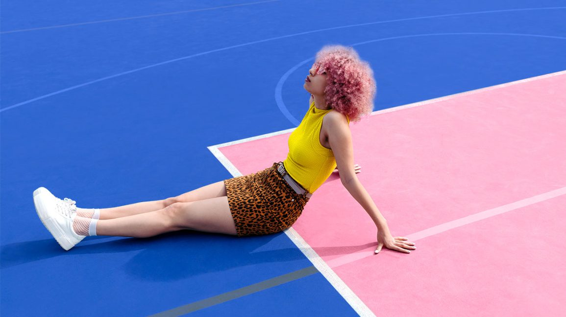 Stylish girl with a pink afro, leopard skirt, and yellow halter top, daydreams while lounging on a pink and blue tennis court.