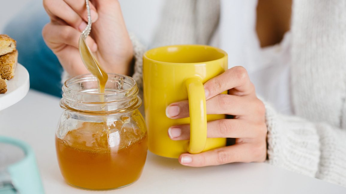 Woman adding honey to her coffee