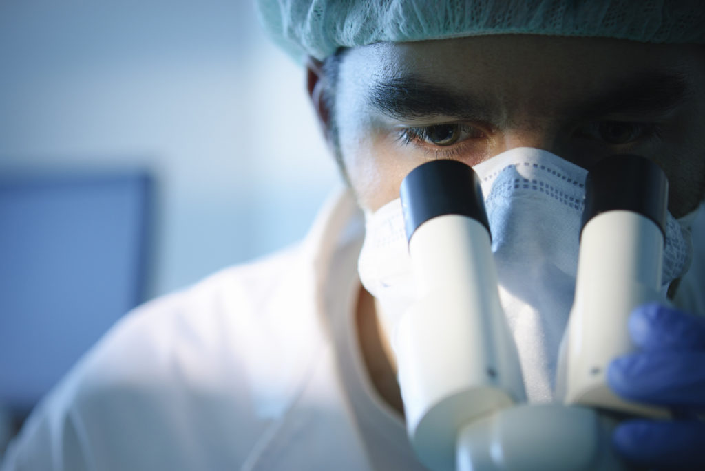 researcher wearing surgical mask peering into microscope