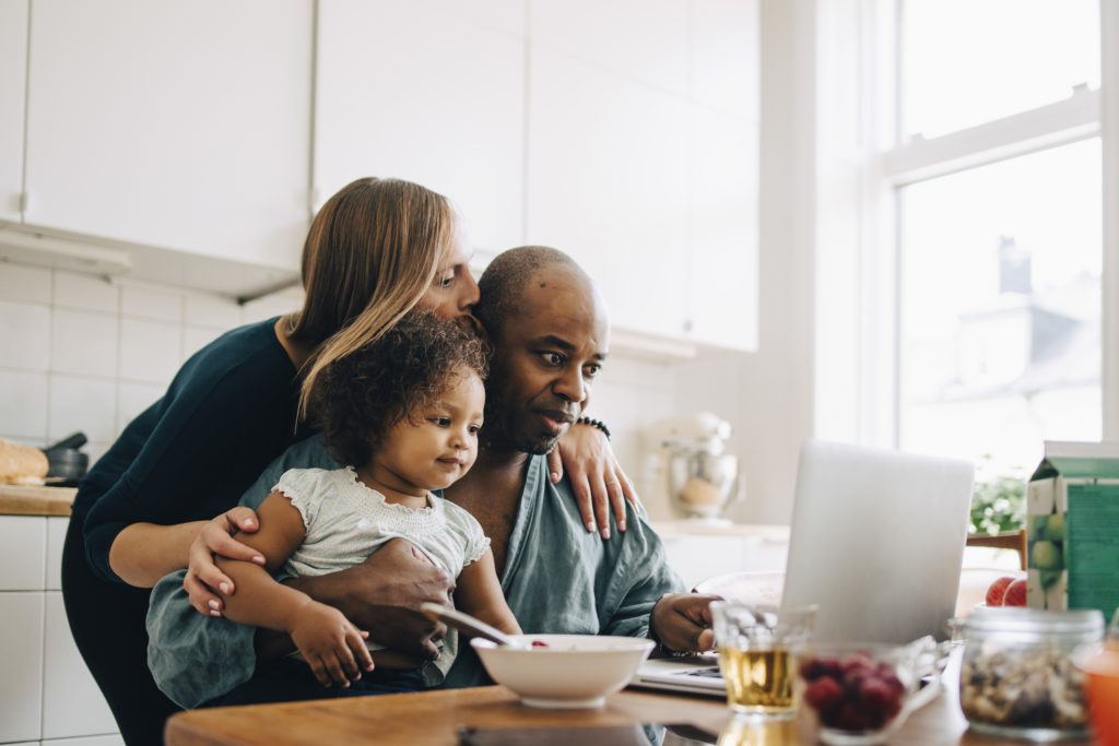 family made up of man, woman, and baby looking at screen on laptop