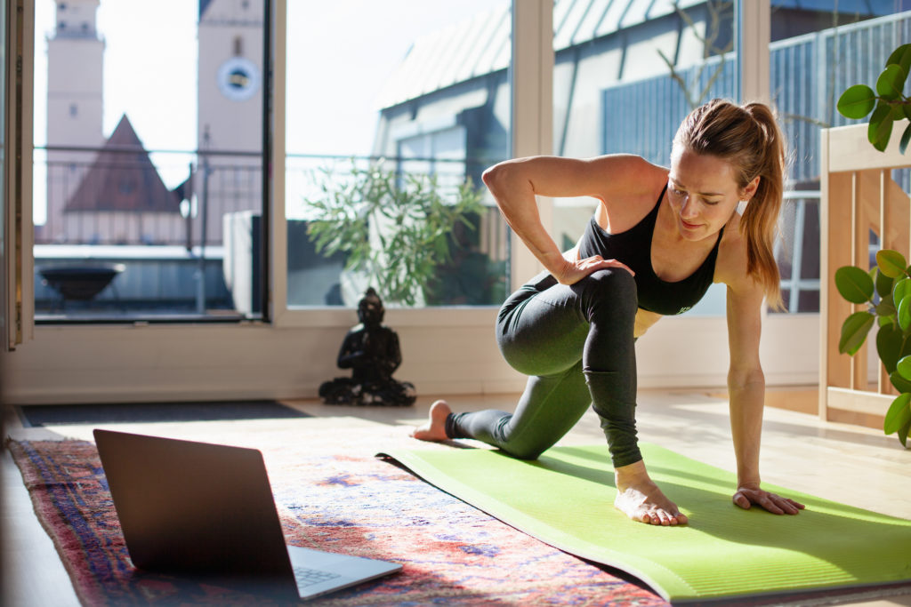 woman doing yoga in front of the computer