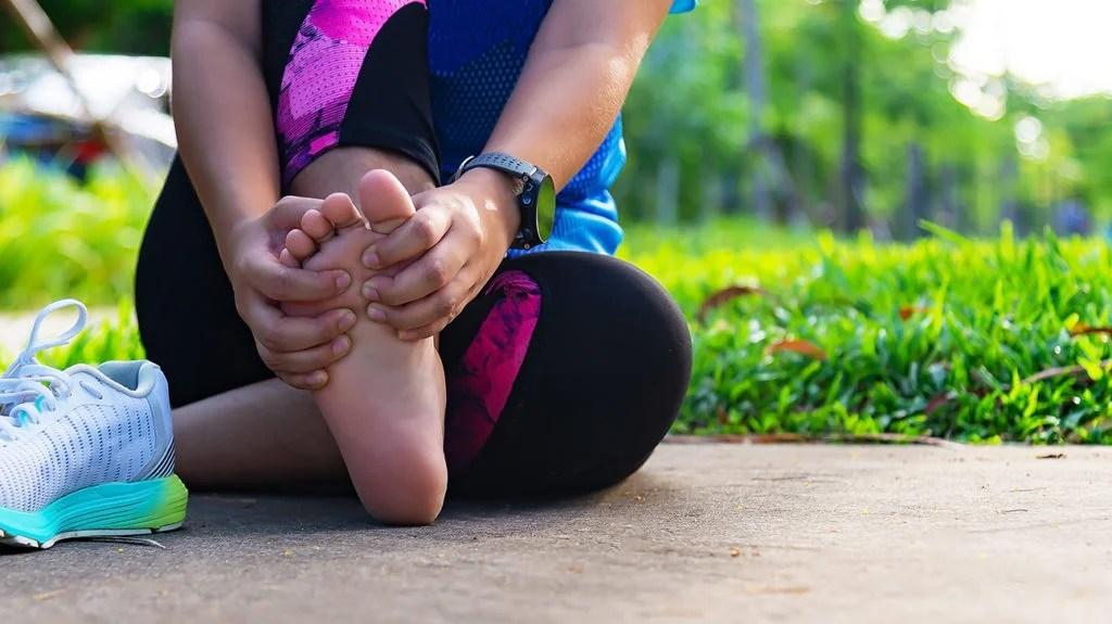 une femme tenant son pied parce qu'elle a mal à la plante du pied