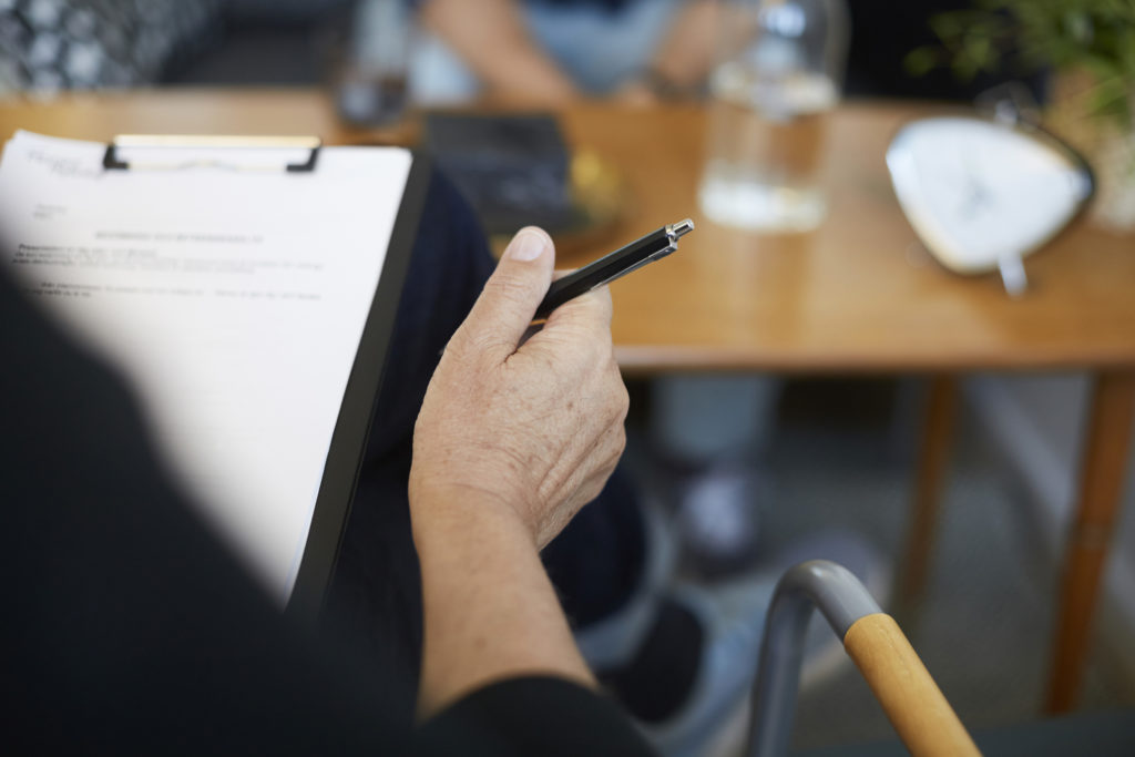 Cropped image of male therapist with reports on clipboard at community center