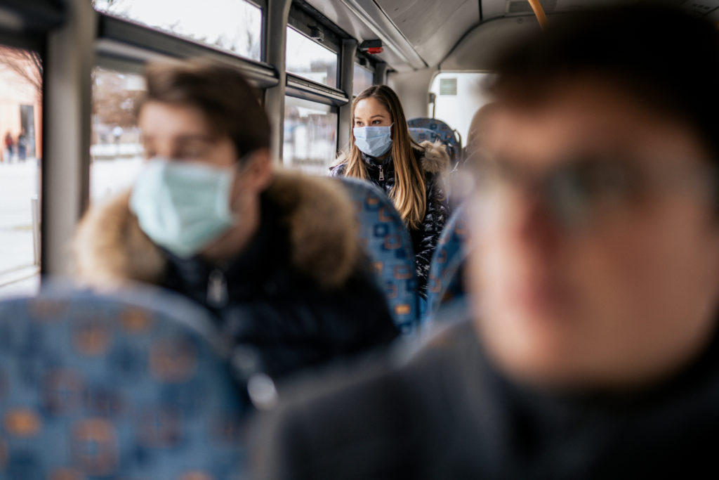woman wearing face mask in the back of a bus