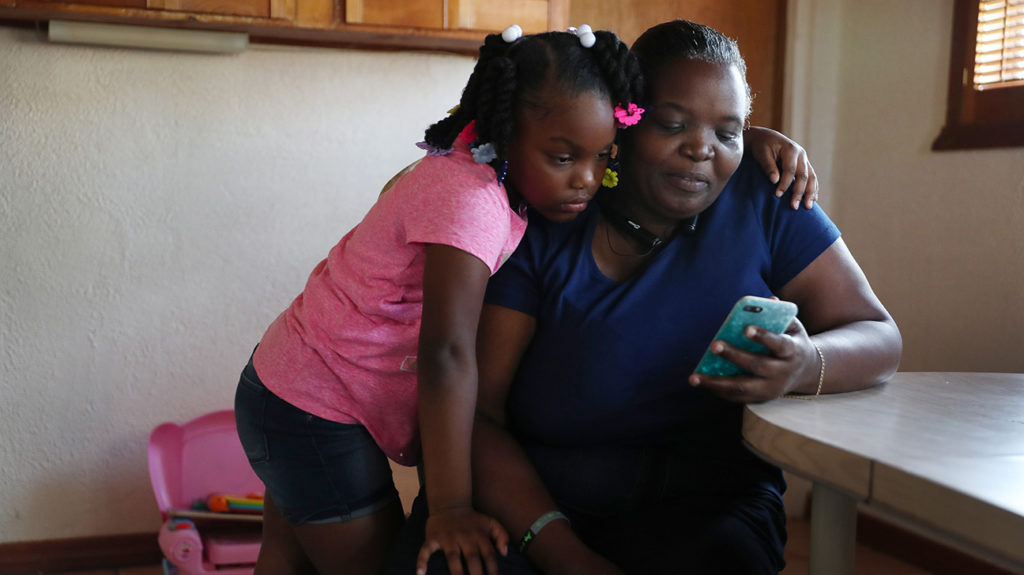 Willie Mae Daniels spends time looking at videos with her granddaughter, Karyah Davis,6, after being laid off from her job as a food service cashier at the University of Miami on March 17 as the university joins in the effort to fight the coronavirus on March 26, 2020 in Miami, Florida. Mrs. Daniels said that she has applied for unemployment benefits as she joins roughly 3.3 million Americans nationwide who are looking for unemployment benefits as restaurants, hotels, universities, stores and more shut down in an effort to slow the spread of COVID-19. (Photo by Joe Raedle/Getty Images)