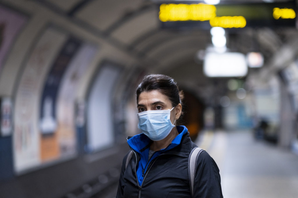 woman wearing mask waiting for the subway
