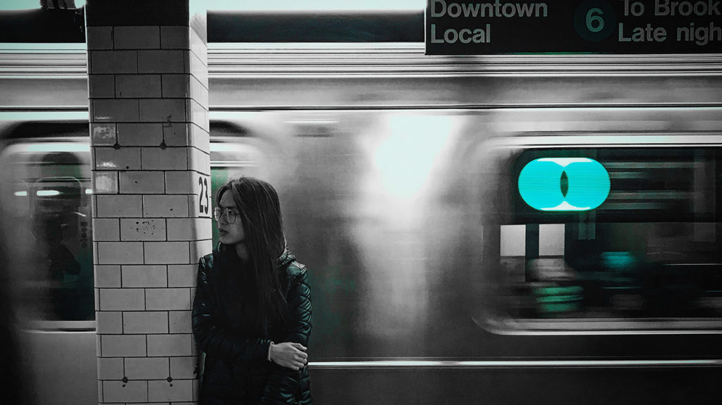 a young asian woman standing in station while a train passes