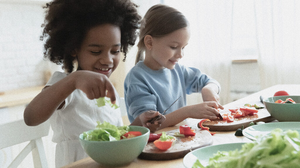 Two children prepare a salad together which contains some of the best vitamins for kids.