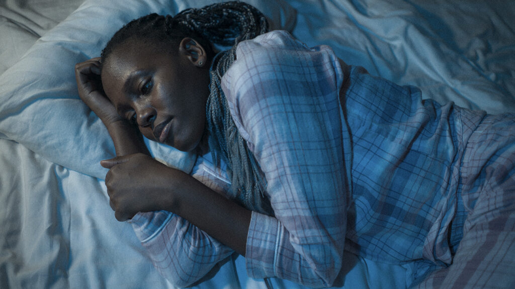 """A Black woman has trouble sleeping in bed, accompanying a Special Features article, """"What makes sleep more difficult for minority groups?"""""""
