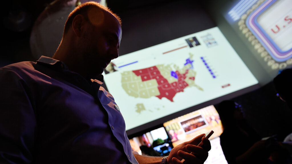 a man walking past an election map while looking at his phone