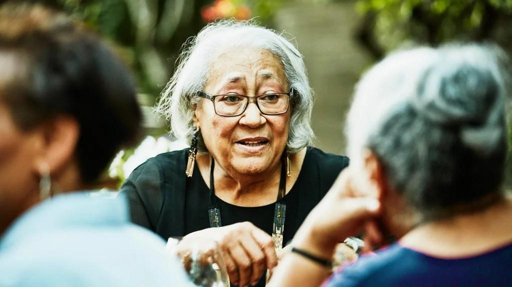 a Black senior woman talking at a gathering outside