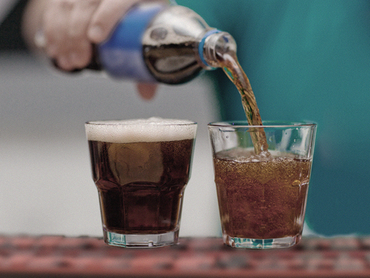close up of a hand pouring coke in two glasses