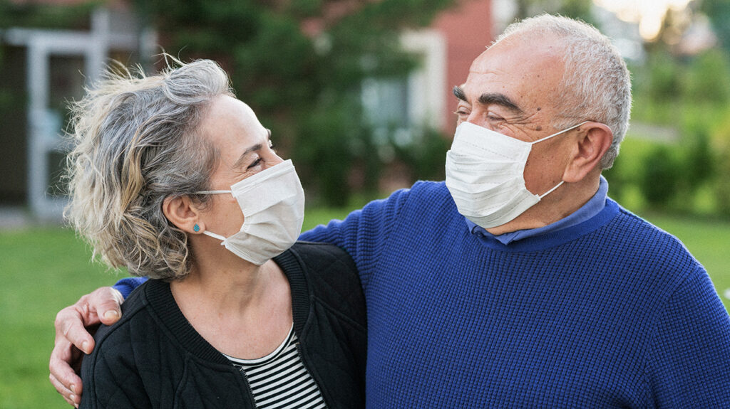 A photo of two happy seniors wearing masks to protect against covid-19.