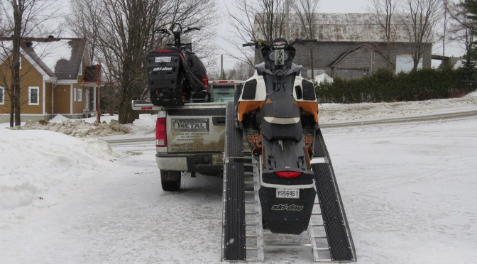Snowmobiles Being Loaded onto Modified DiamondBack Truck Bed Cover