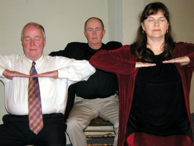 Photo: three adults doing a breathing exercise with arms positioned across chest