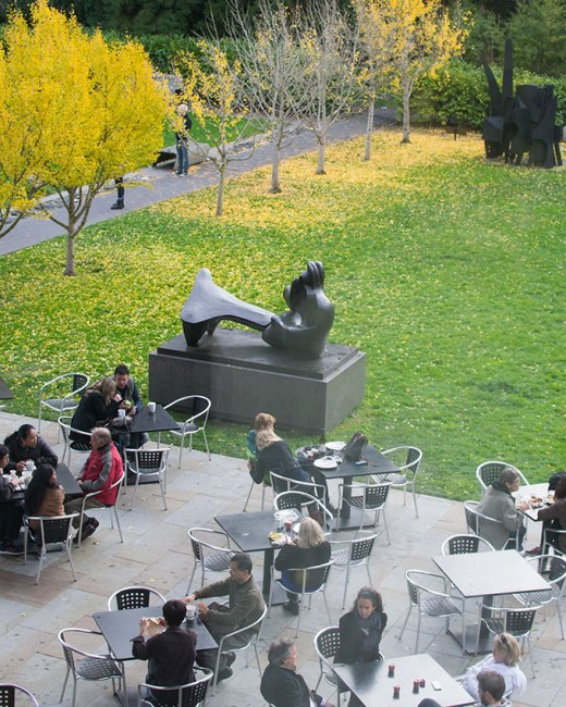 Photo: people seated in museum open-air cafe at the museum in autumn