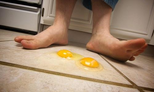 Eggs on the Floor at Man's Feet