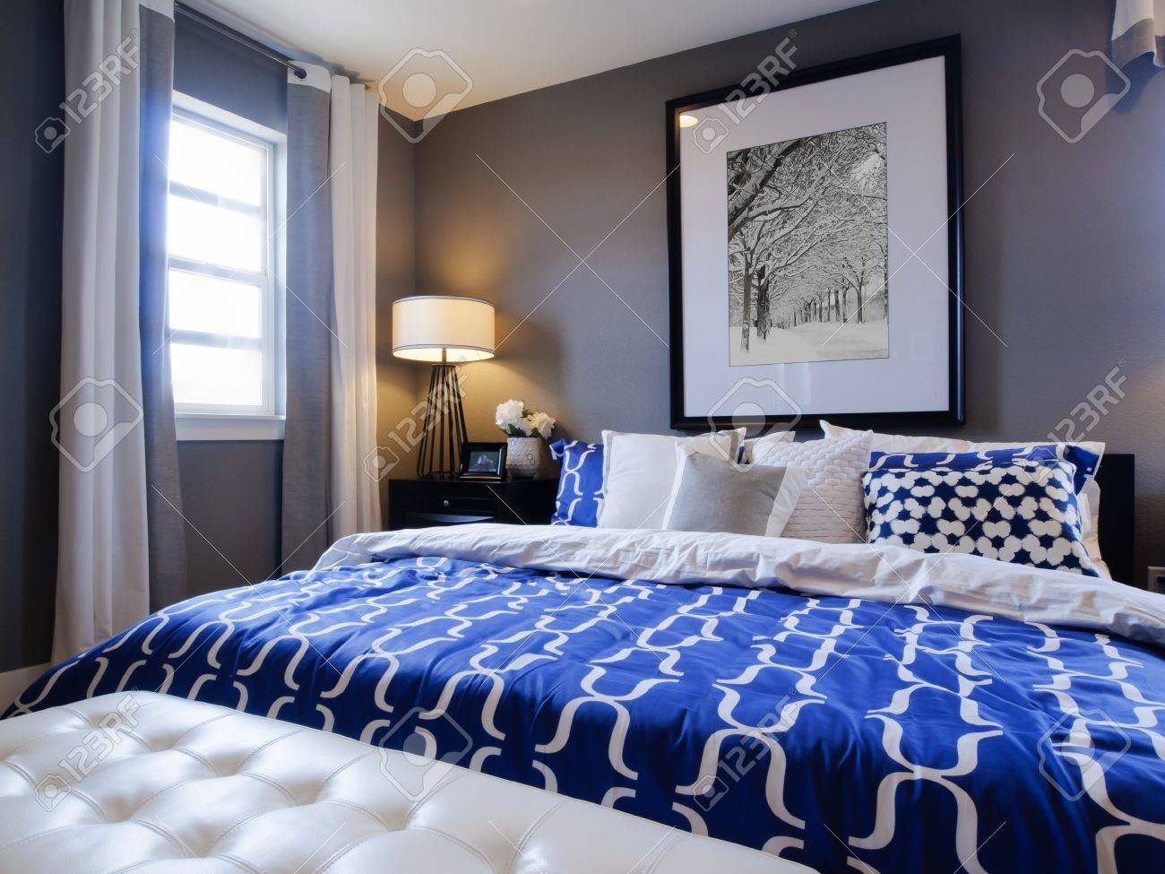Modern master bedroom with blue wall and white linens stock photo 15079294