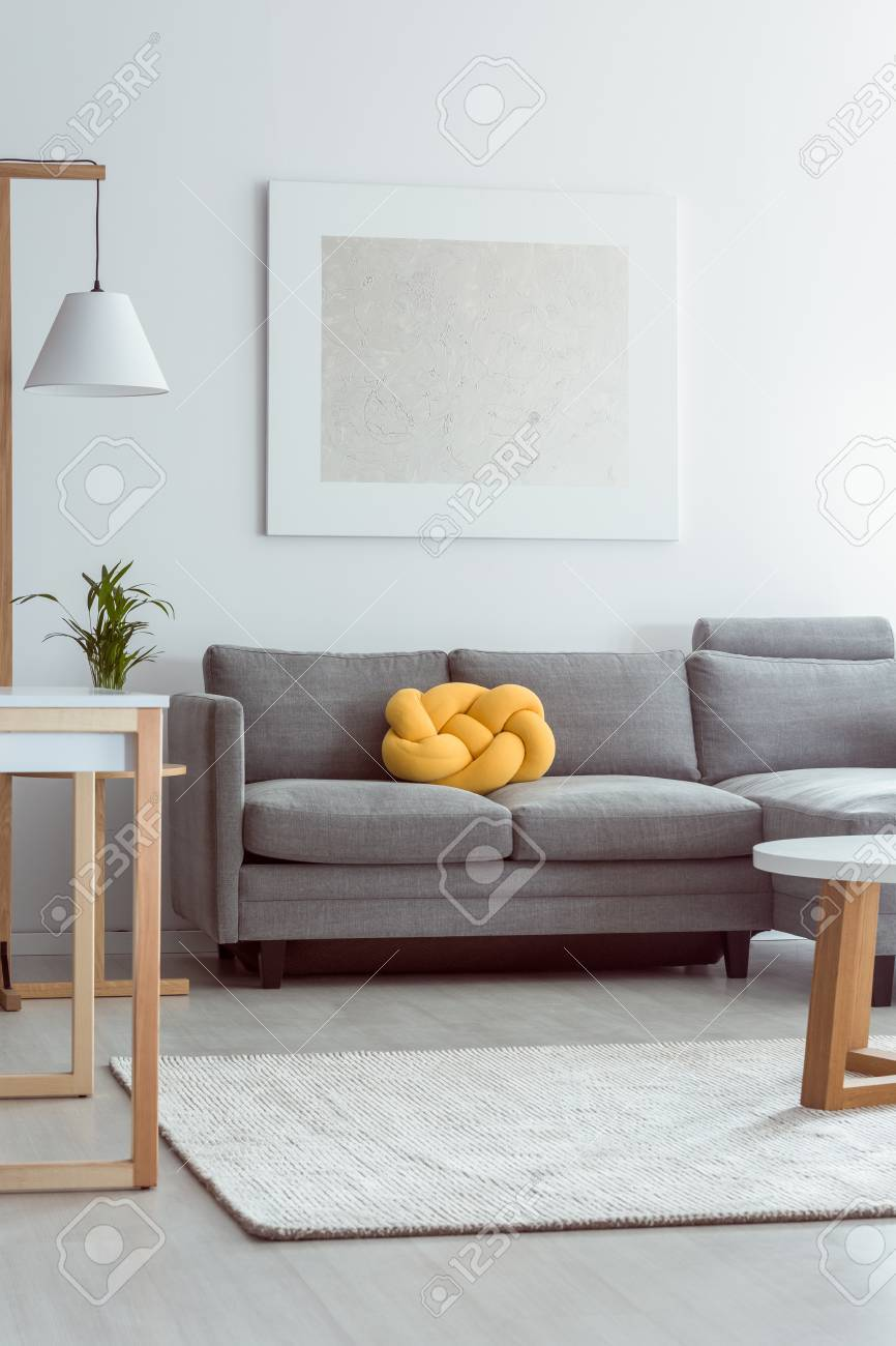 Living Room With Grey Sofa Yellow Knot Pillow On Grey Sofa In Cozy Living Room With White