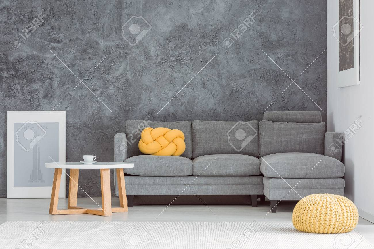 Couchtisch Pouf Yellow Pouf In Front Of Grey Sofa Against Concrete Wall In Living