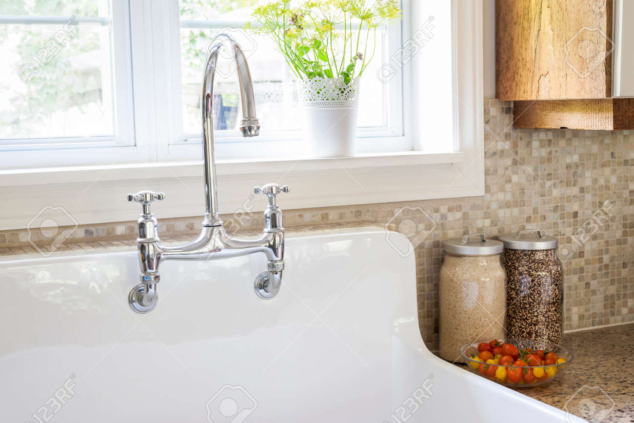 35893317 Rustic white porcelain kitchen sink with curved faucet and tile backsplash under large window Stock Photo