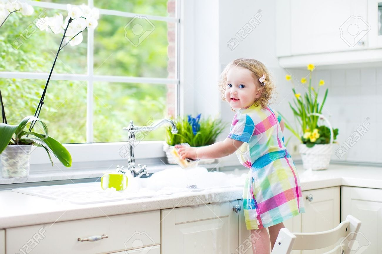 30781195 Cute curly toddler girl in a colorful dress washing dishes cleaning with a sponge and playing with f Stock Photo