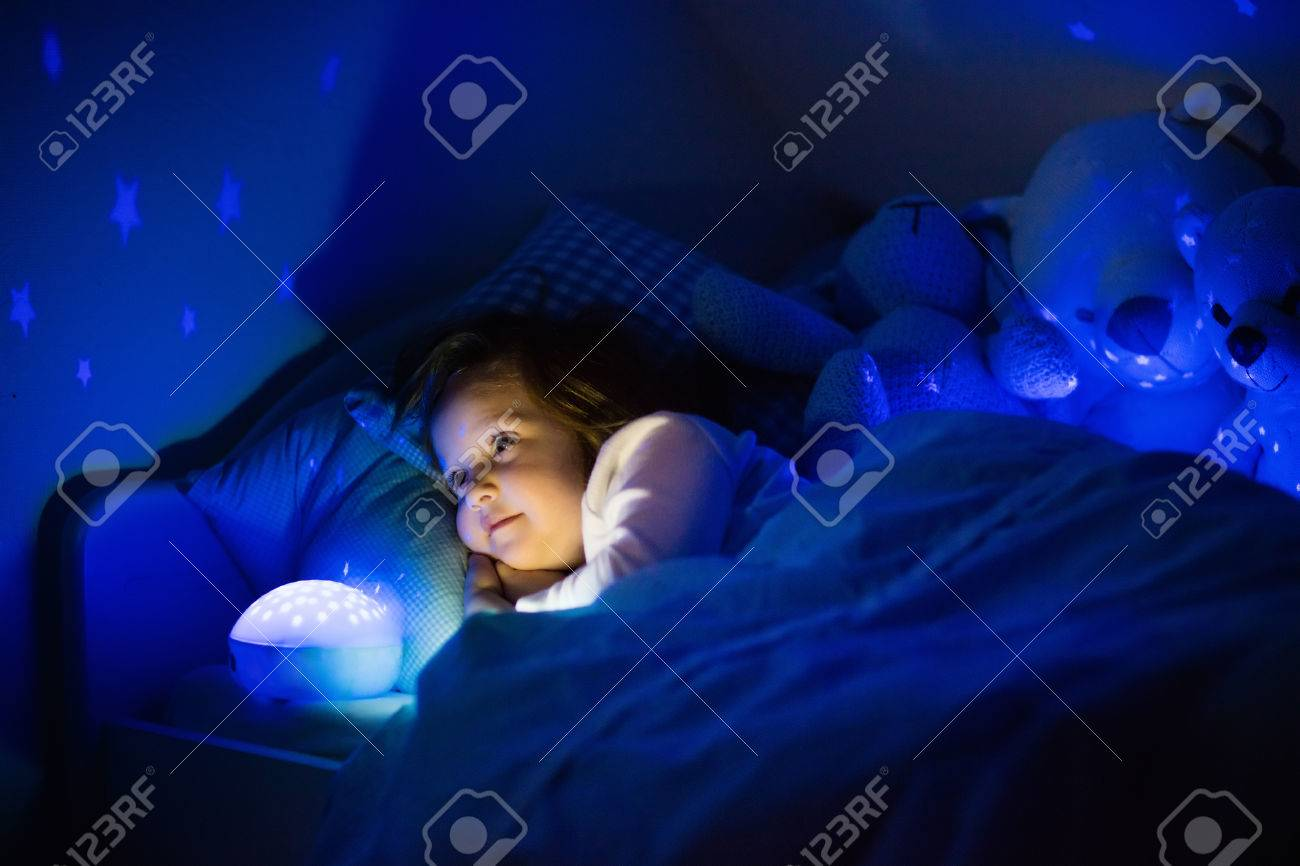 Night Light With Stars On Ceiling Little Girl Reading A Book In Bed Dark Bedroom With Night Light