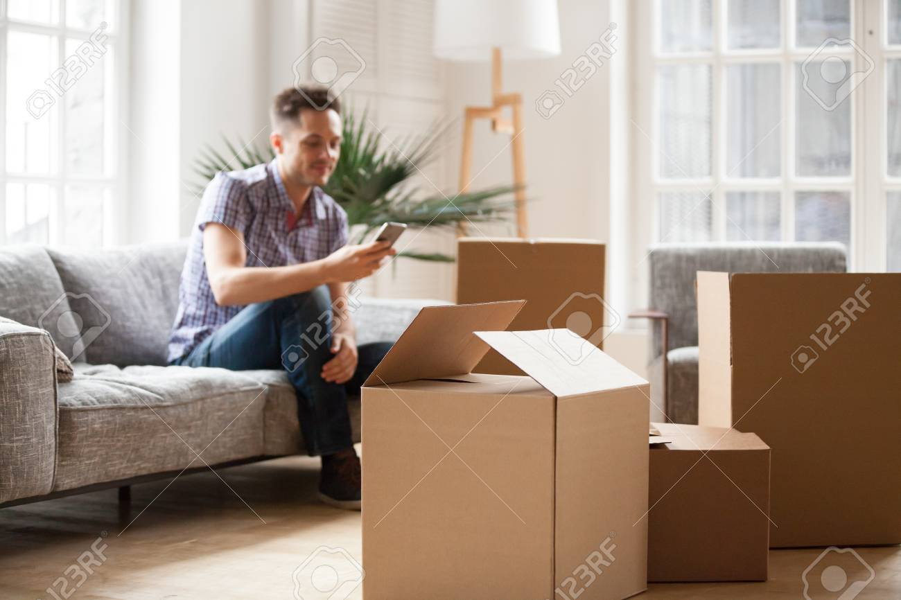 Sofa Service Packed Cardboard Boxes With Young Man Sitting On Sofa In Living