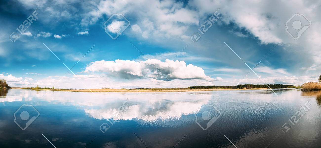 River Or Lake Landscape With Reflections Of Cloudy Sky In Water