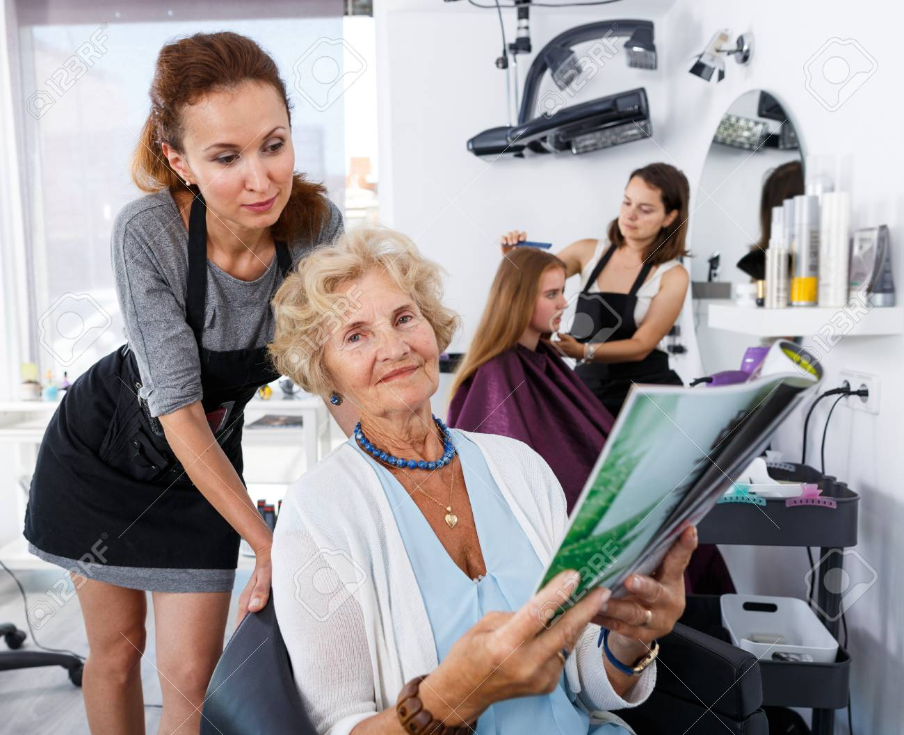 Salon Senior Young Woman Hairdresser In Hair Salon Helping To Senior Woman