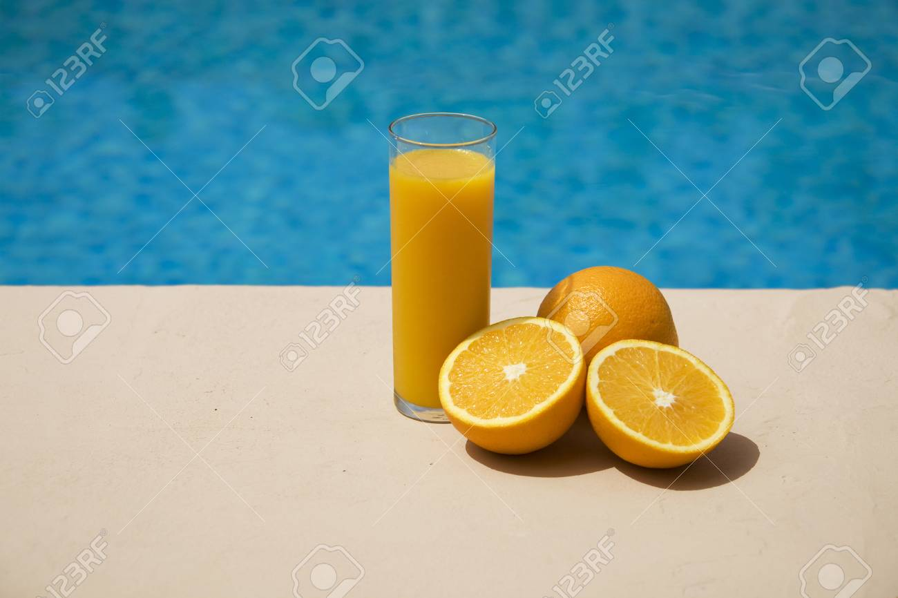 Glas Pool Glas With Orange Juice And Oranges At The Swimming Pool Side