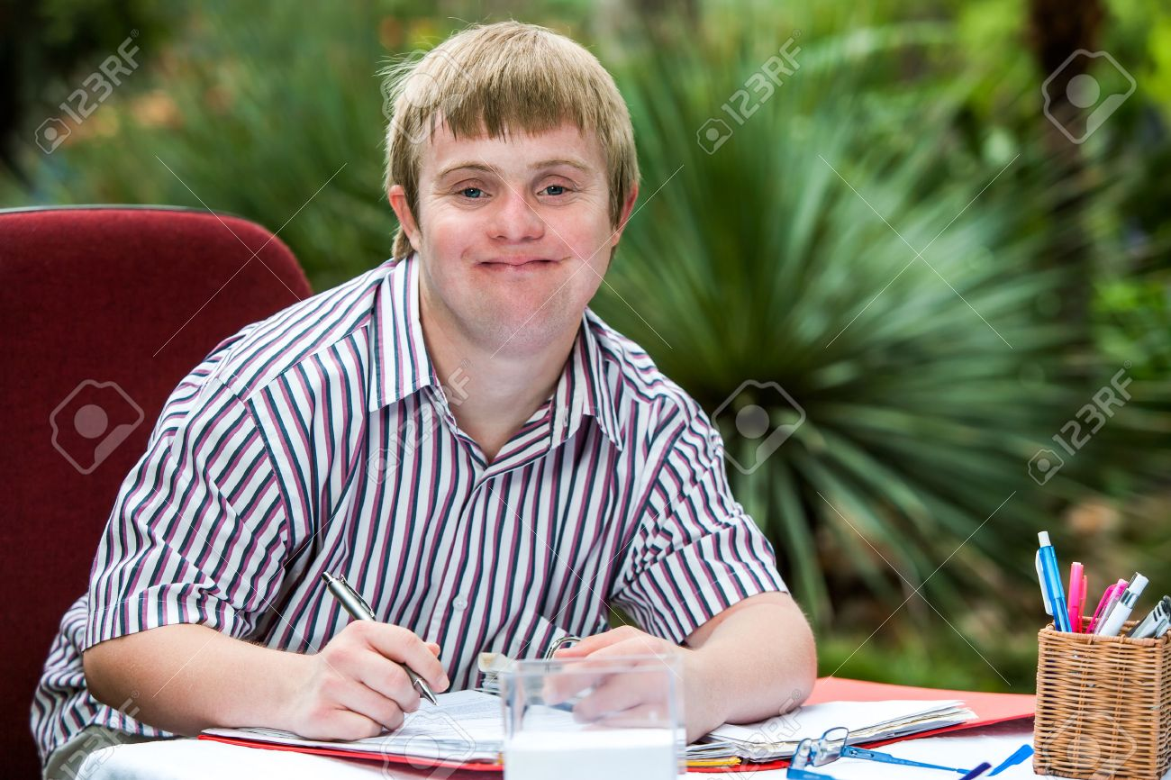 Down syndrome adult close up portrait of young male student with down syndrome at study
