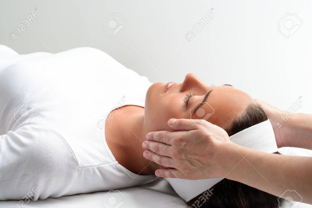 Healing Treatment Close Up Of Practitioner Doing Reiki With Hands On Young Woman